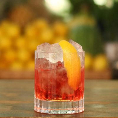 A Negroni cocktail resting on the top of a bar