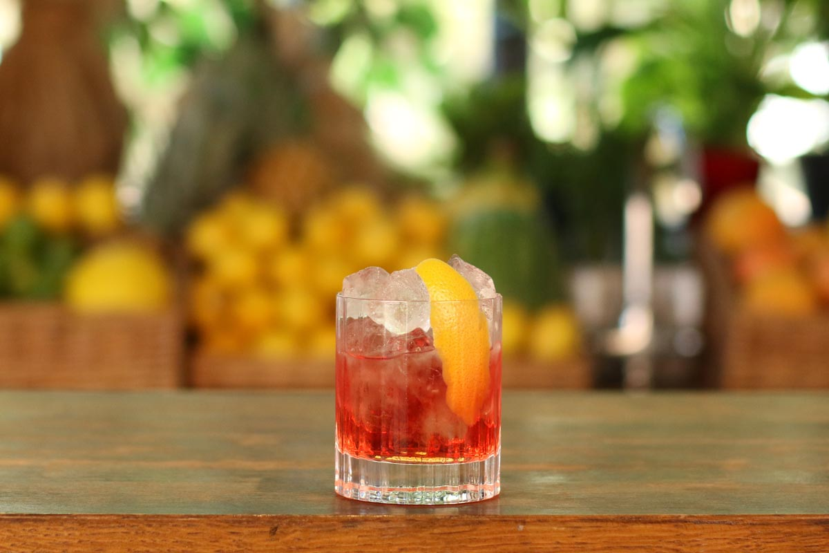 How to make A Negroni, a cocktail resting on the top of a bar