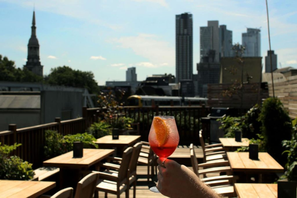 A man holds an Aperol Spritz on the roof terrace, with east London's skyline in the background.