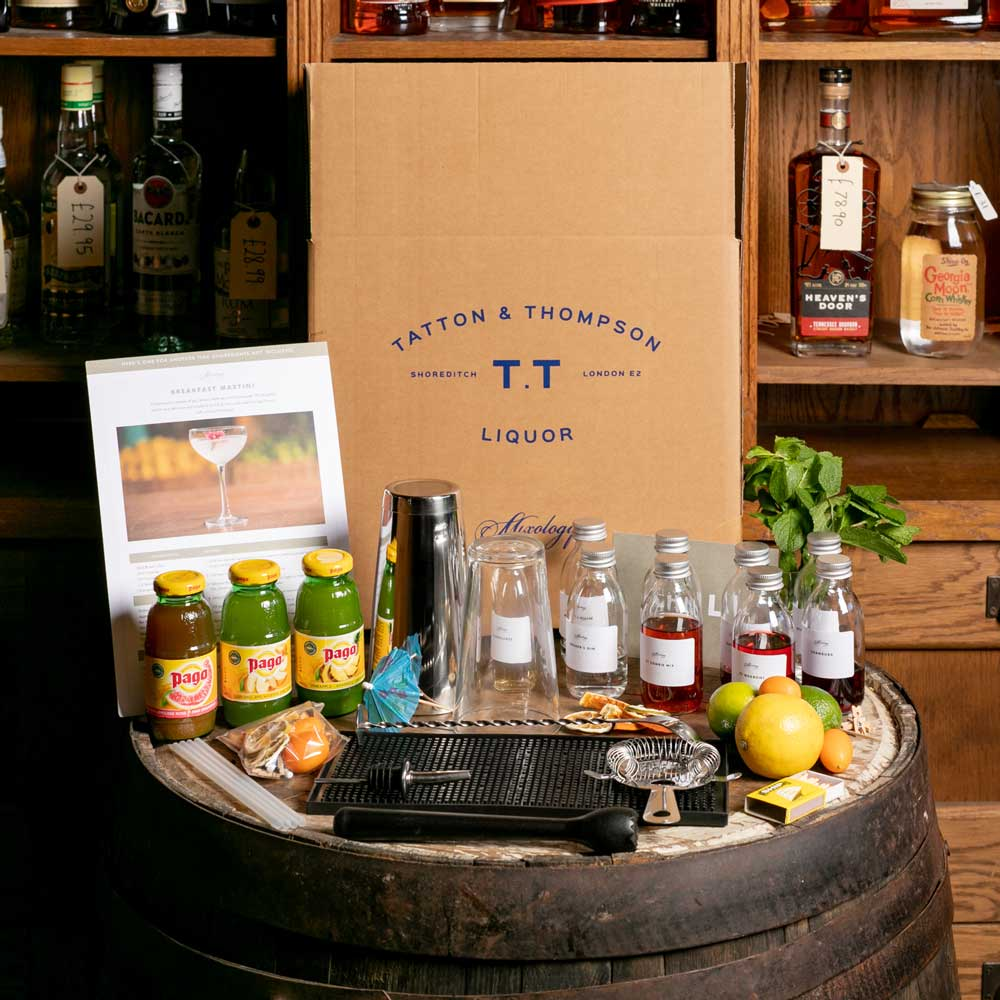 Image of all the ingredients and equipment contained in a TT Liquor virtual class box, laid out on a barrel.