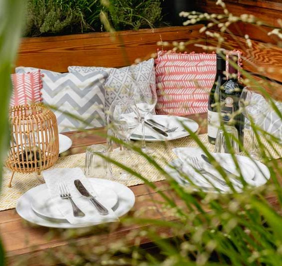 A picture of one of the dining tables on TT Liquor's roof terrace, prepared for dinner with plates and cutlerly laid out